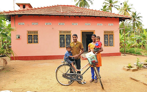 Thajeekaran family outside their permanent home.