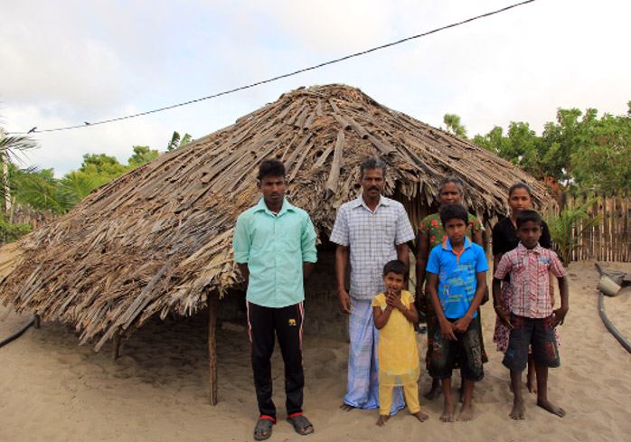 The Sivarasa family outside their temporary shelter.