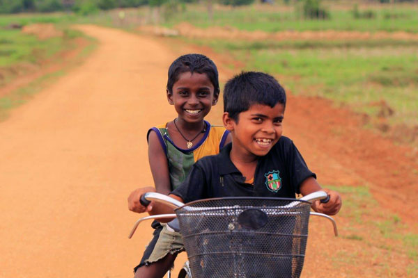 Children cycling along the newly rehabilitated road in Eralakulam.