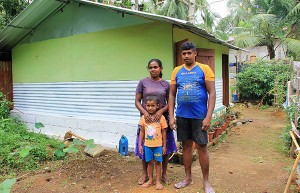 Ravindra Mithrajith, Kusumawathie and their son outside their new home.