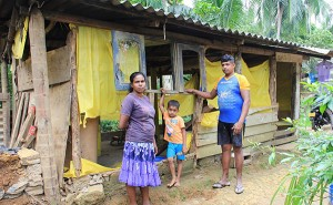 The family next to their old home damaged by the flood.