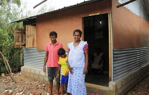 Swarnakanthi, Priyantha and their second son outside their new shelter